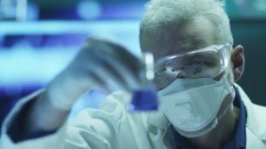 Scientist in Safety Glasses is Inspecting Chemical Reagents in Flask. Close-up. — Stock video