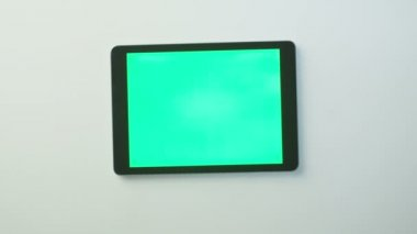 Hands are Putting Tablet PC with Green Screen on the White Table and Starting to Use it. Great for Mock-up Usage — Vidéo