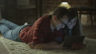 Young Happy Smiling Couple using Tablet PC for Entertainment at Home at Evening Time. Casual Lifestyle. — Stock Video