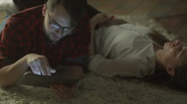 Young Couple are Laying on the Floor and Relaxing at Evening at Home using Tablet PC. Casual Lifestyle — Stock Video