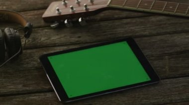 Tablet PC with Green Screen Laying on Wooden Table next to Guitar and Headphones. Causal Lifestyle — Stok video
