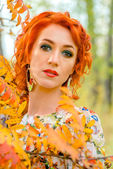 Red-haired girl with yellow leaves — Stock Photo