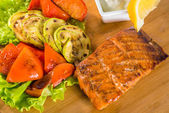 Salmon steak with grilled vegetables, sauce and lemon — Stock Photo