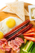 Toasts, fried eggs, sausages, meat and vegetables — Stock Photo