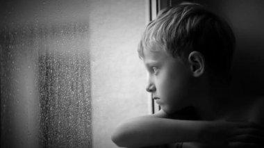 Alone little boy looks raindrops through window glass — Stock Video