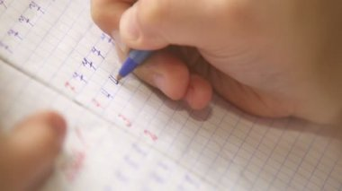 First steps in writing: little pupil write digits in square grid notebook — Stock Video