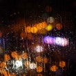 Blurry night city lights in the rain as seen through a wet glass with running water droplets  Batumi, Georgia. — Stock Video #77417508