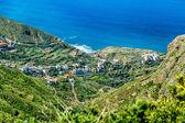 Village in green valley near ocean — Stock Photo