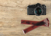 Camera and photographic 35 mm film strip on wooden background — Stock Photo