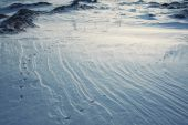 Rocks and snow surface texture with bird traces in evening sunli — Foto de Stock