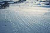 Rocks and snow surface texture with bird traces in evening sunli — Stock Photo