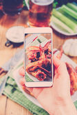 Using smartphone to take photos of BBQ — Stock Photo