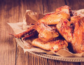 Roasted wings on wooden background — Stock Photo