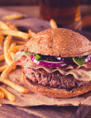 Burger and french fries close up on vintage style. — Stock Photo