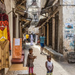 Local people on a typical narrow street in Stone Town, Zanzibar — Stock Photo #64312559