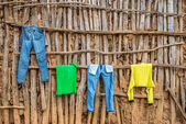 Clothes hanging on wall of a wooden hut in Africa — Stock Photo