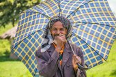 Old ethiopian man with an umbrella on a hot day — Stock Photo