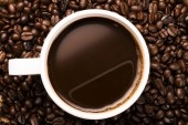 Cup of hot coffee on coffee beans — Стоковое фото