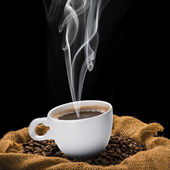 Cup of hot coffee on coffee beans — Stock Photo