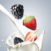 Blackberries with strawberries Fall Into Milk Splash — Stock Photo