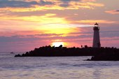 Lighthouse with searchlight beam in sunset — Stock Photo