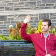 Man waving to somebody from a bench — Stock Photo #57230193