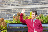 Man waving to somebody from a bench — Stock Photo