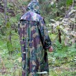 A man in a camouflage hooded standing back in the woods with a k — Stock Photo #53110429