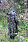 A man in a camouflage hooded standing back in the woods with a k — Stock Photo
