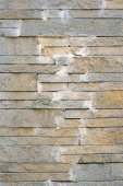 A fence made of beige narrow stones fastened by cement as backgr — Stock Photo