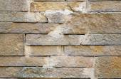 A fence made of beige stones fastened by cement as background — Stock Photo