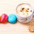 French colourful macaroons and a cup of coffee. - Macro shot wit — Stock Photo #70456787