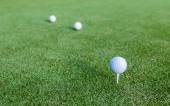 Golf ball and tee on green grass during training at golf club. — Stock Photo