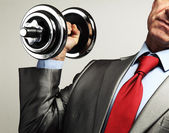 Image of businessman in suit raising dumbbell. Tax burden concep — Stock Photo