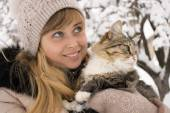 Beautiful girl in mittens with a fluffy cat in winter — Stok fotoğraf