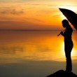 Silhouette of a girl with an umbrella in the sunset on the beach — Stock Photo #67399597
