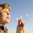 Young girl blow bubbles against the blue sky — Stock Photo #70137519
