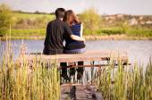 Love couple sitting on the bridge on the river bank — Stock Photo