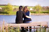 Man embraces girl sitting on a pier at the river bank — Stock Photo