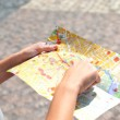 Pretty young female tourist studying a map — Stock Photo #53992431