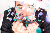 Young man blowing confetti — Stock Photo