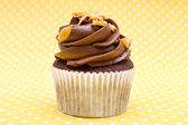 Cupcakes on yellow polka dot background — Stock Photo