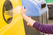 Throwing a bottle into the recycling container — Stock Photo