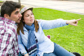 Young man and young woman smiling in park — Stock Photo