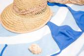 Summer hat, shell and bikini on towel — Stock Photo