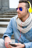 Man listening to music in the street — Stock Photo