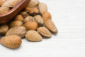 Almonds in a bowl and wooden utensils — Stockfoto