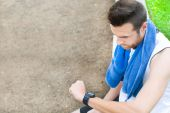 Man doing running and watching the watch in park — Stock Photo