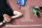 Man lying on the running track — Stock Photo