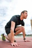 Man ready to run on the track — Stock Photo